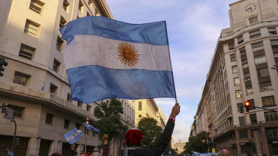 Hombre sostiene una bandera de Argentina.