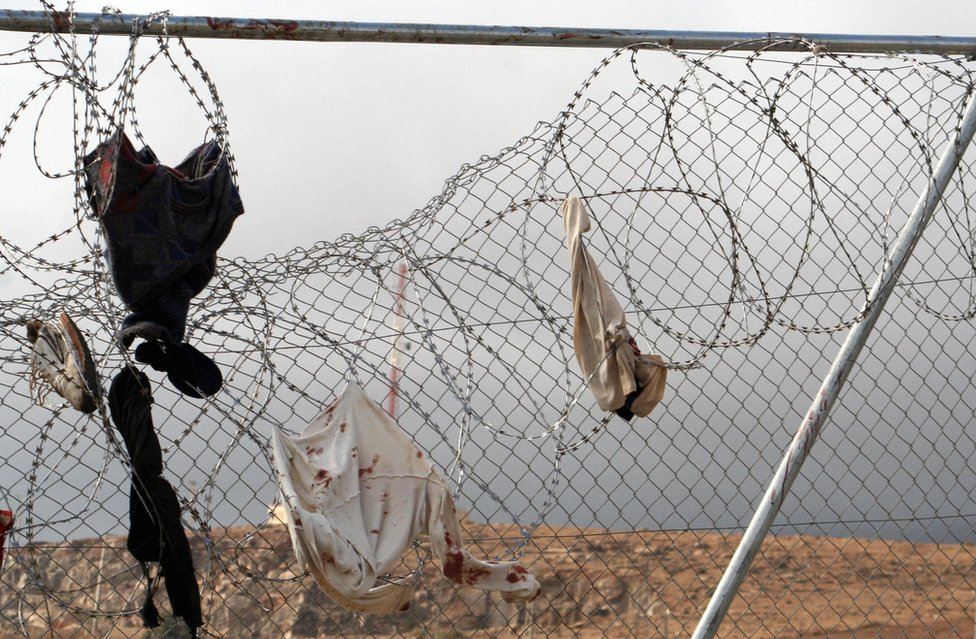 Blood-stained clothing hangs from the razor wire after a mass assault on the double fence into the Spanish enclave of Melilla from Morocco by African immigrants in October 2005