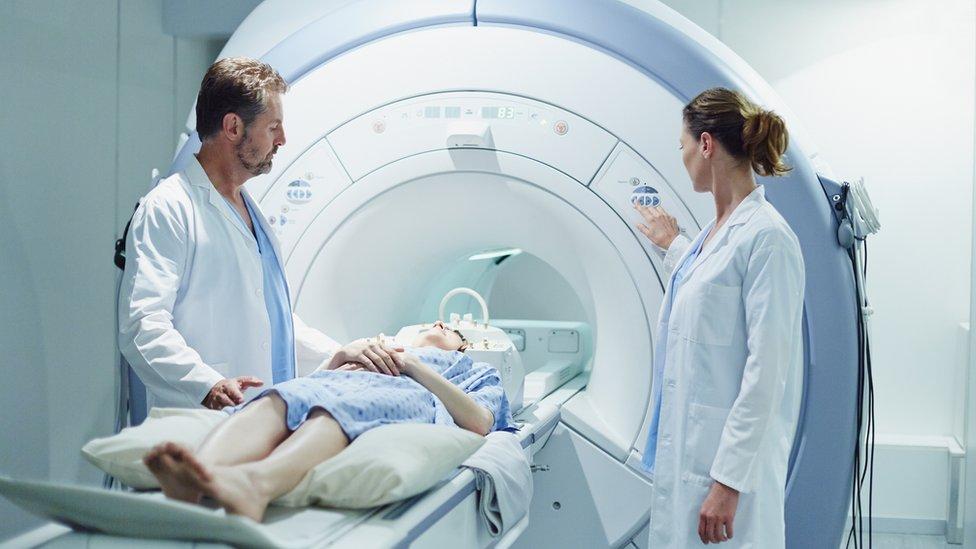 Un doctor y una doctora preparan a una paciente para una IRM.