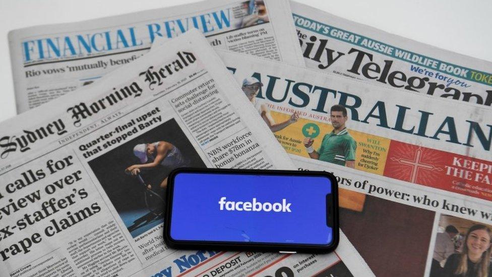 Un celular con el logo de Facebook sobre periódicos australianos