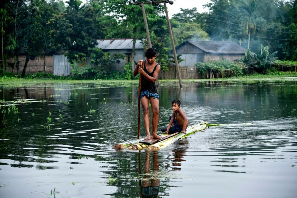 बाढ़ के पानी पर नाव चलाते बच्चे