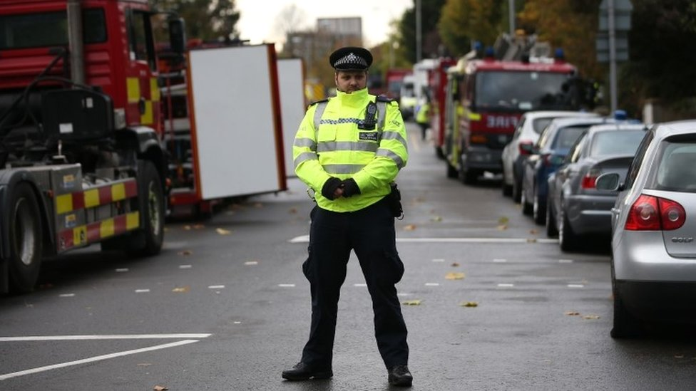 A police officer stands on duty near to the scene of a derailed tram, in Croydon,