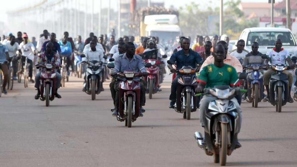 People ride their mopeds out on the streets the morning after the military barracks of the elite presidential guard (RSP) was taken over in Ouagadougou, 30 September 2015