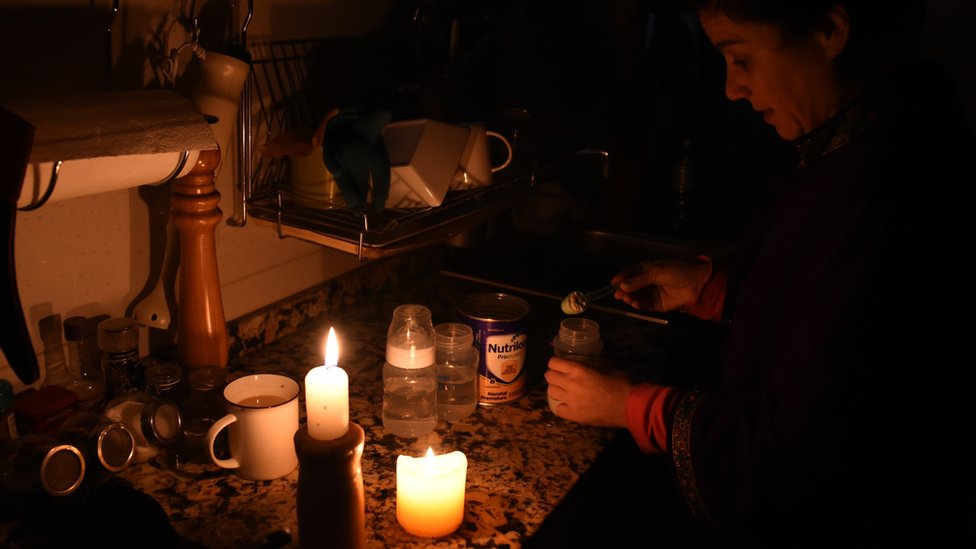 A woman prepares milk bottles using candles at her home in Montevideo on June 16, 2019 during a power cut