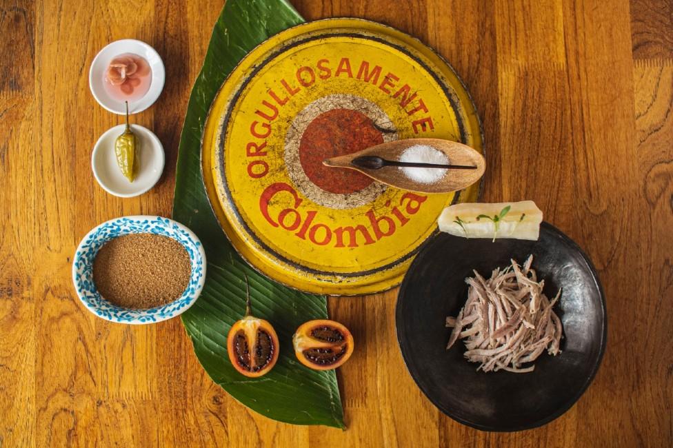 Una mesa con recipientes que contienen ingredientes naturales de Colombia