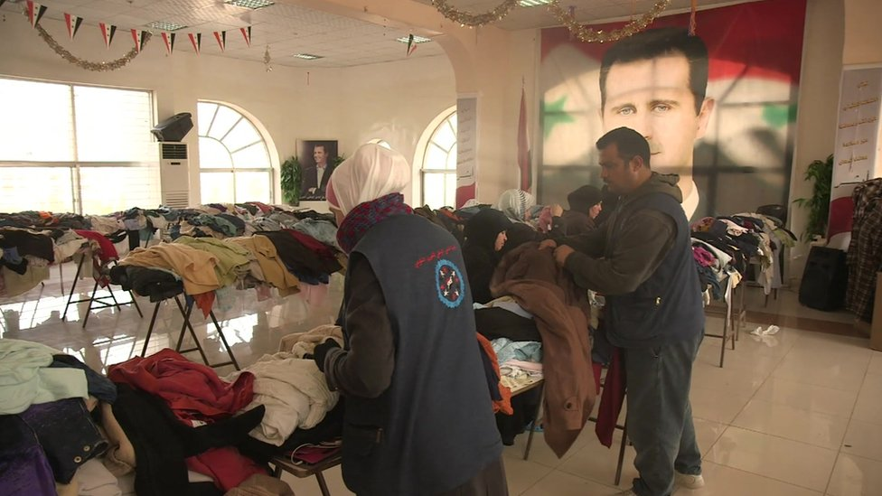 People sort through donated clothes at a shelter for internally displaced people in Damascus