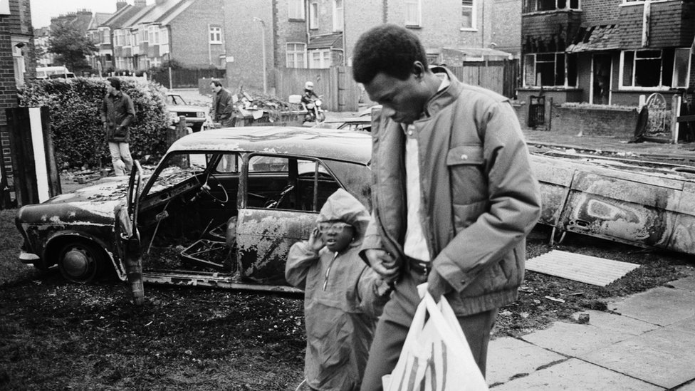 A man and a little girl the day after the Broadwater Farm riots on 6 October 1985