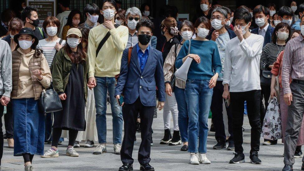 Personas caminando en la calle con mascarillas.