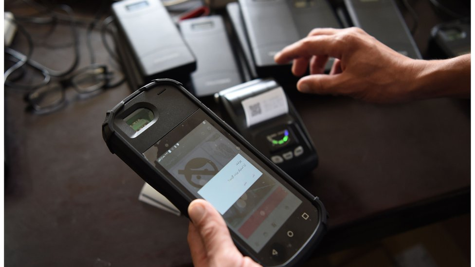 An Independent Election Commission worker tests a biometric device at a warehouse in Kabul.