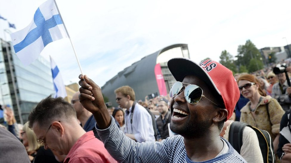 """Participant of a demonstration called """"We have a Dream - Multiculturalism is not a nightmare"""" waves a Finnish flag in Helsinki, Finland, on July 28, 2015"""
