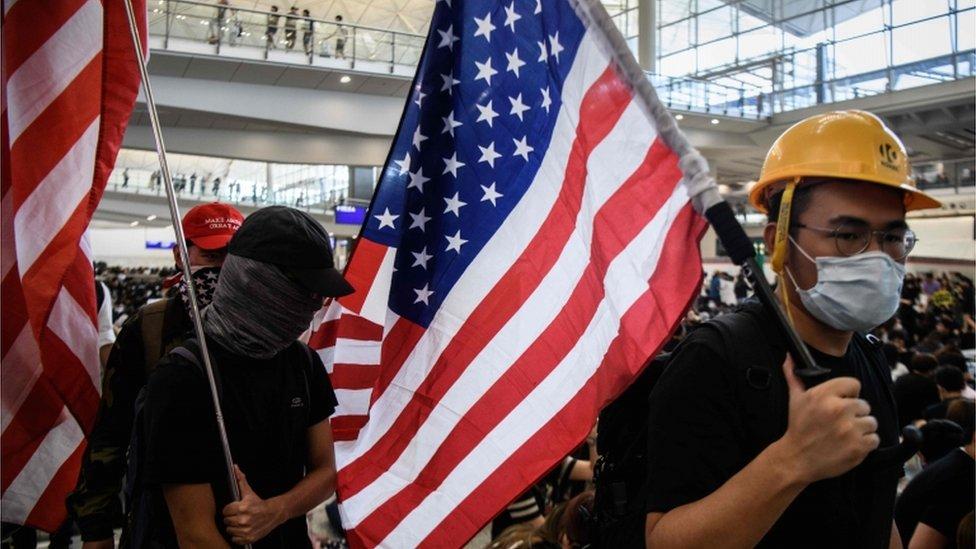 Activists at Hong Kong airport carrying US flags, 9 August 2019