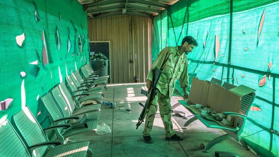 Un soldado afgano inspecciona las pertenencias dejadas atrás por el ejército de EE.UU. tras su salida de la base aérea de Bagram