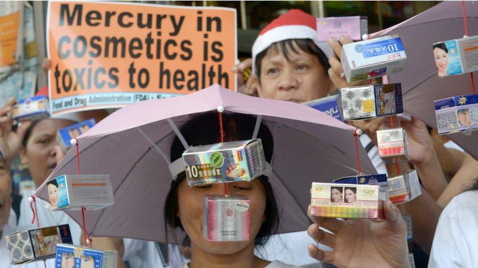 Manifestantes realizan una manifestación frente a una farmacia en Manila, mostrando productos supuestamente adulterados con mercurio