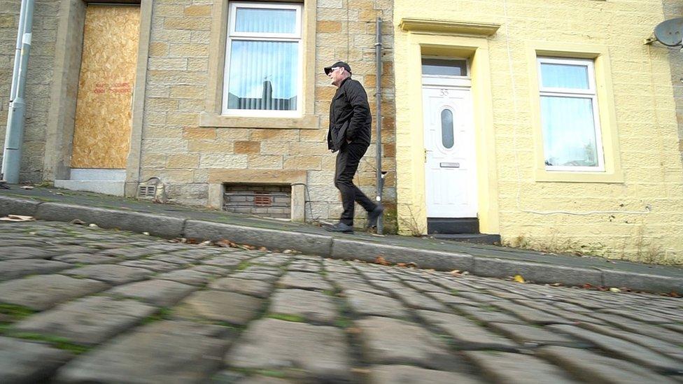 Mick Fleming caminando por las calles de Burnley.