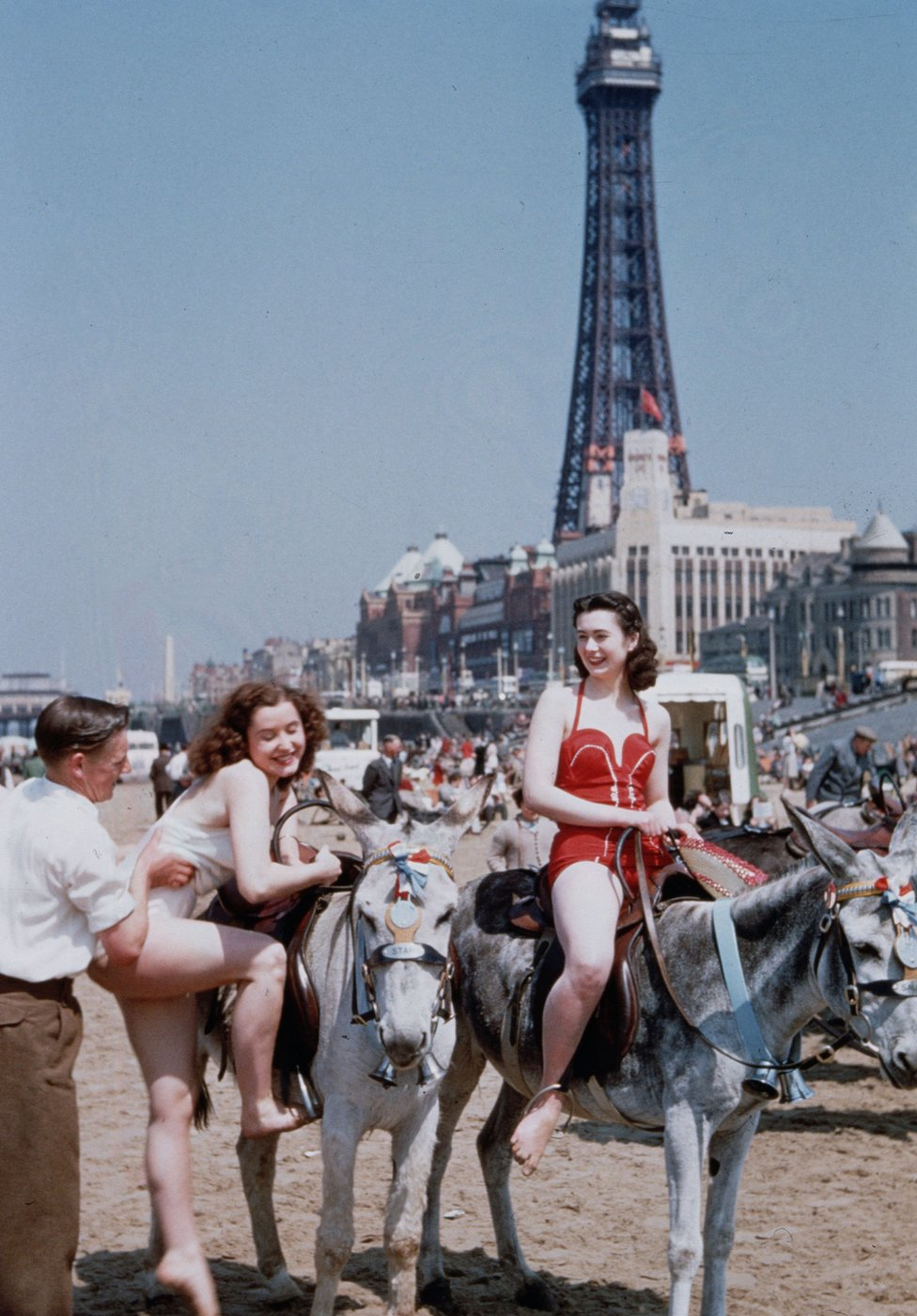 Holiday-makers riding donkeys on the beach at Blackpool