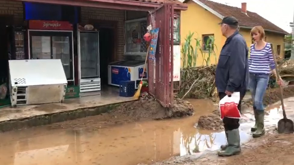 Žena sa lopatom i čovek u gumenim čizmama gledaju u potopljenu seosku prodavnicu.