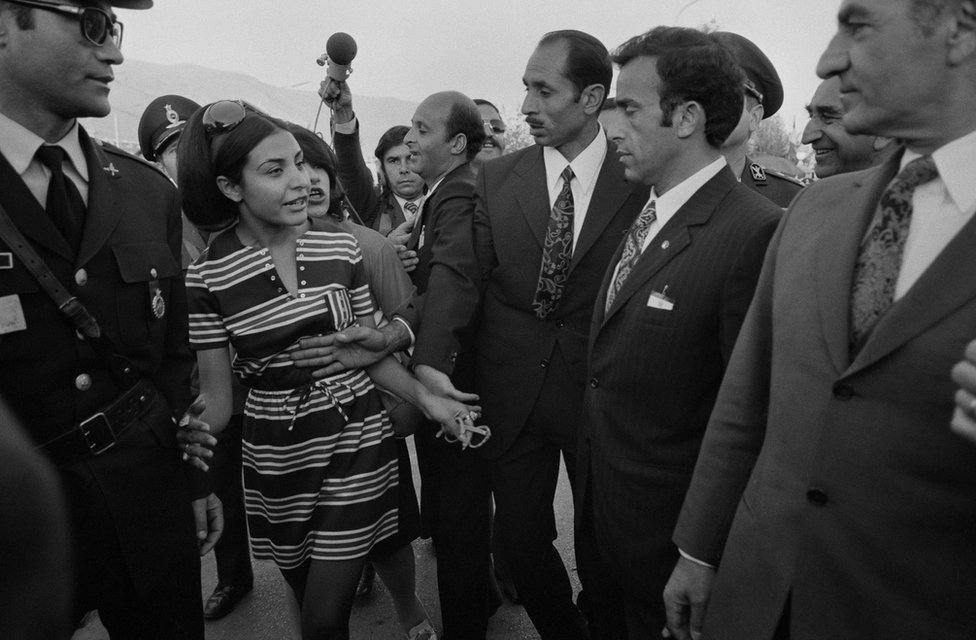 Bodyguards intervene when a young Iranian woman wants to talk to Shah Mohammad Reza Pahlavi who is visiting, with Queen Farah, the press centre of the Persepolis celebration in 1971