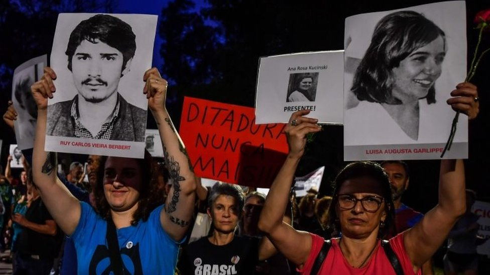 People holding pictures of people who were killed or went missing during the 1964-1985 dictatorship, demonstrate on the 55th anniversary of the military coup, at Ibirapuera Park, in Sao Paulo, Brazil, on March 31, 2019