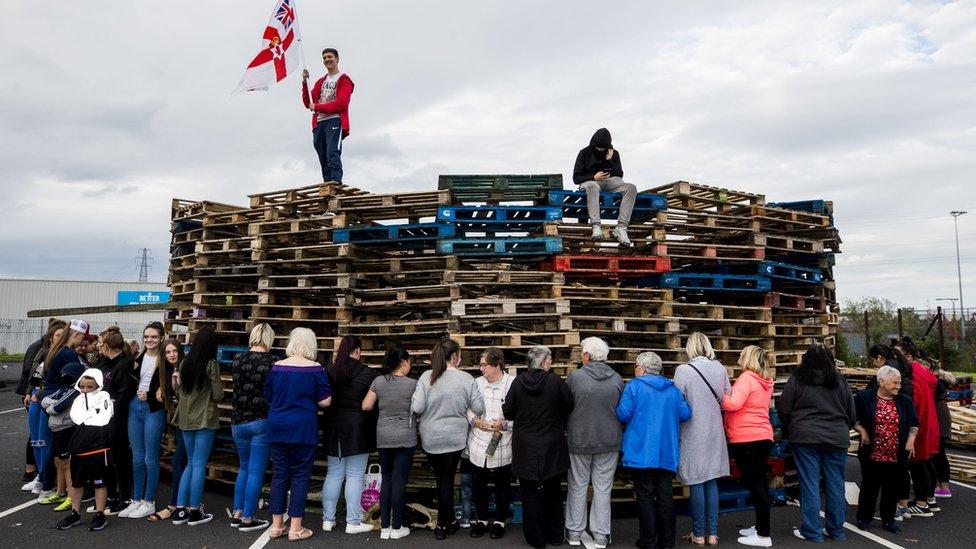 Woman surround the loyalist bonfire at Avoniel Leisure Centre