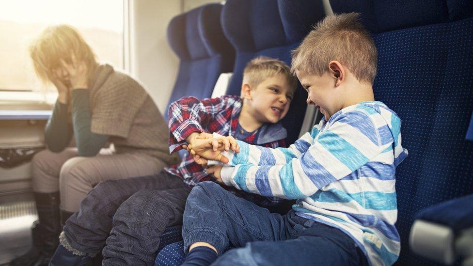 Una mujer en un tren con dos niños traviesos al lado