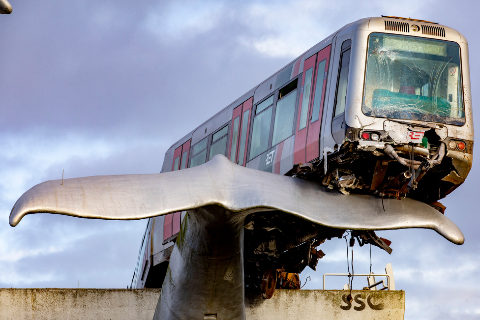 A damaged metro train rests on the tail of a whale sculpture