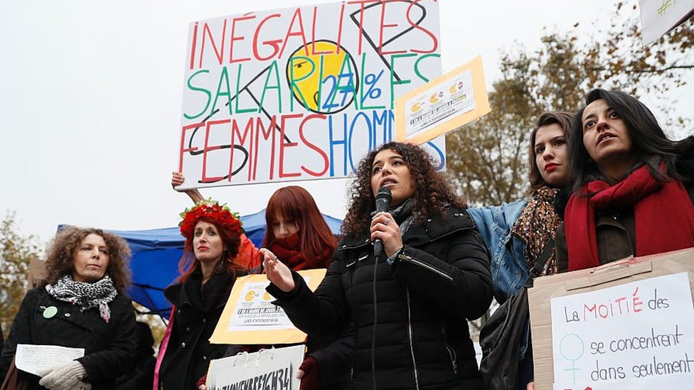 Women stage a protest over pay inequality at the place de republique