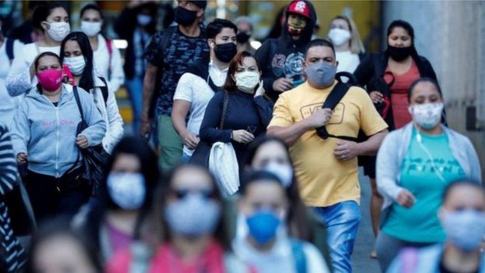 Pessoas andando com máscaras na rua