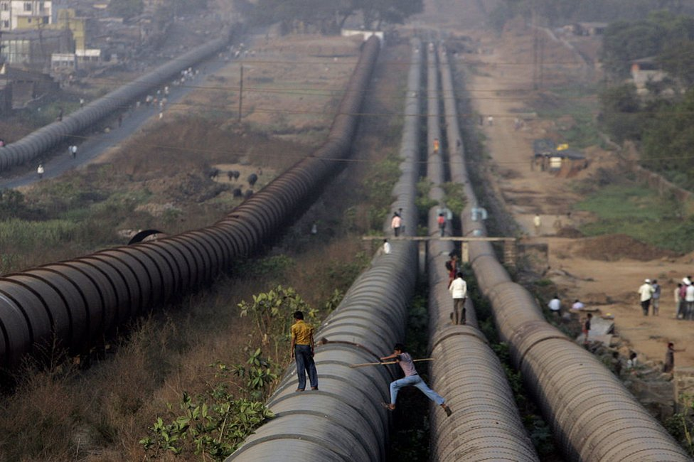 Locals walk on the Tansa water pipeline