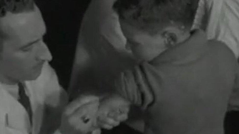 Homem vacinando criança na Escócia