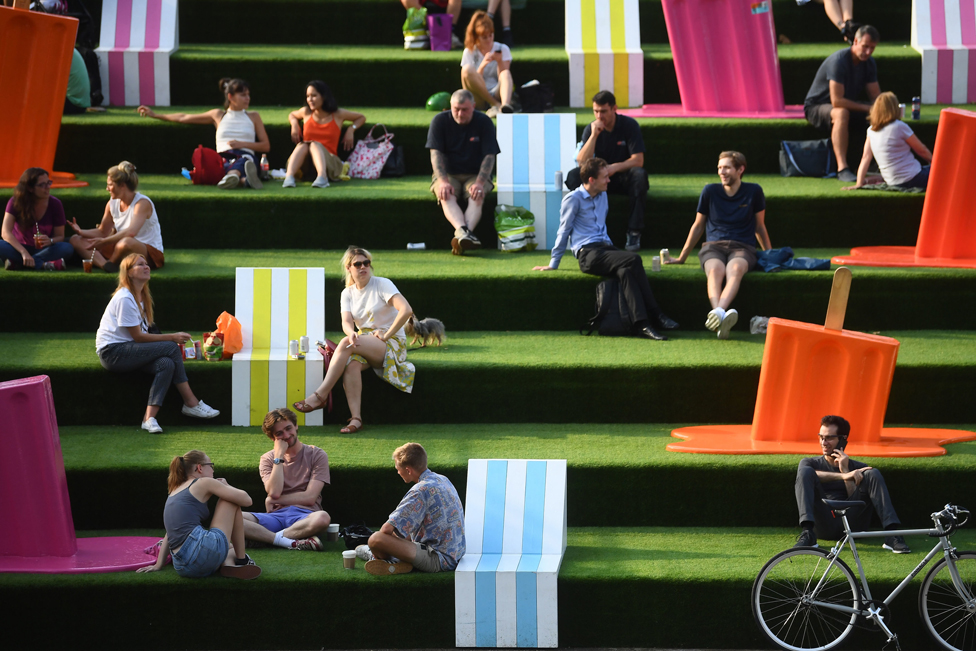 Groups of people sit on green steps outdoors, next to sculptures of melting ice lollies