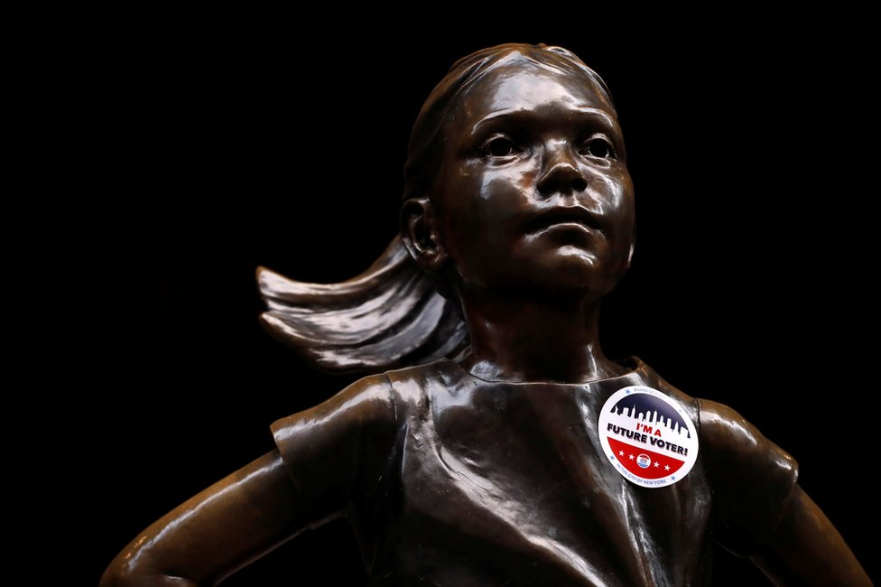 A statue of a girl with a voting sticker on it