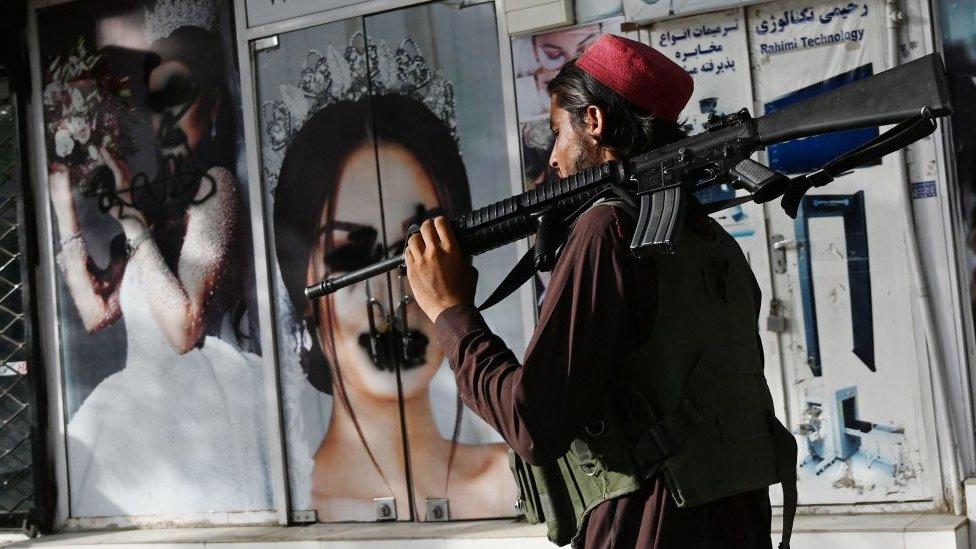 Bir Taliban üyesi, sprey boyayla kapatılmış kadın fotoğrafları bulunan bir güzellik salonunun önünden geçiyor.