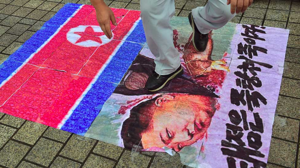 South Korean activist tramples on an caricature picture of North Korean leader Kim Jong-Un during a protest in Seoul