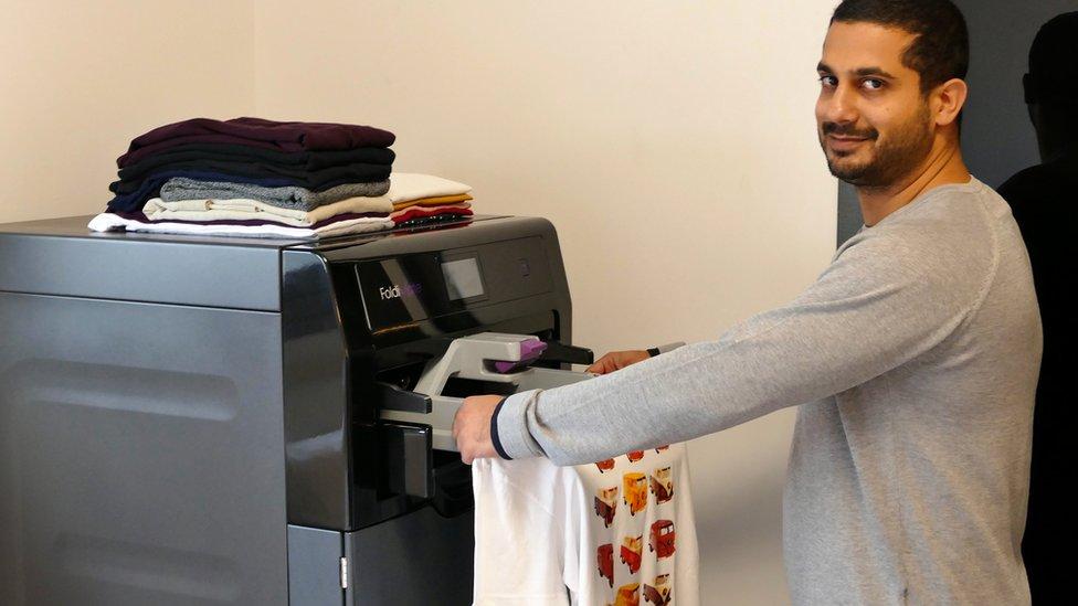 A man uses Foldimate to automatically fold clothes