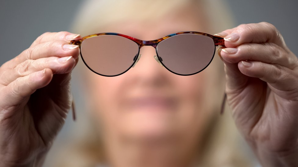 Blurred out face of a mature woman holding a pair of glasses with blurred lenses