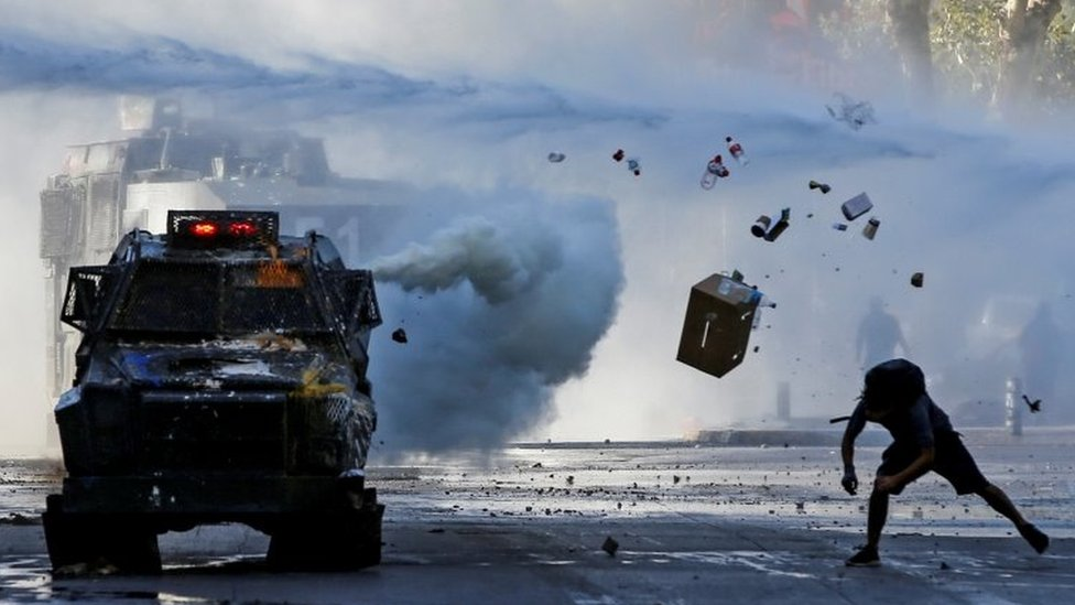 """A demonstrator throws items at an armoured vehicle during a protest against Chile""""s government in Santiago, Chile December 30, 2019."""