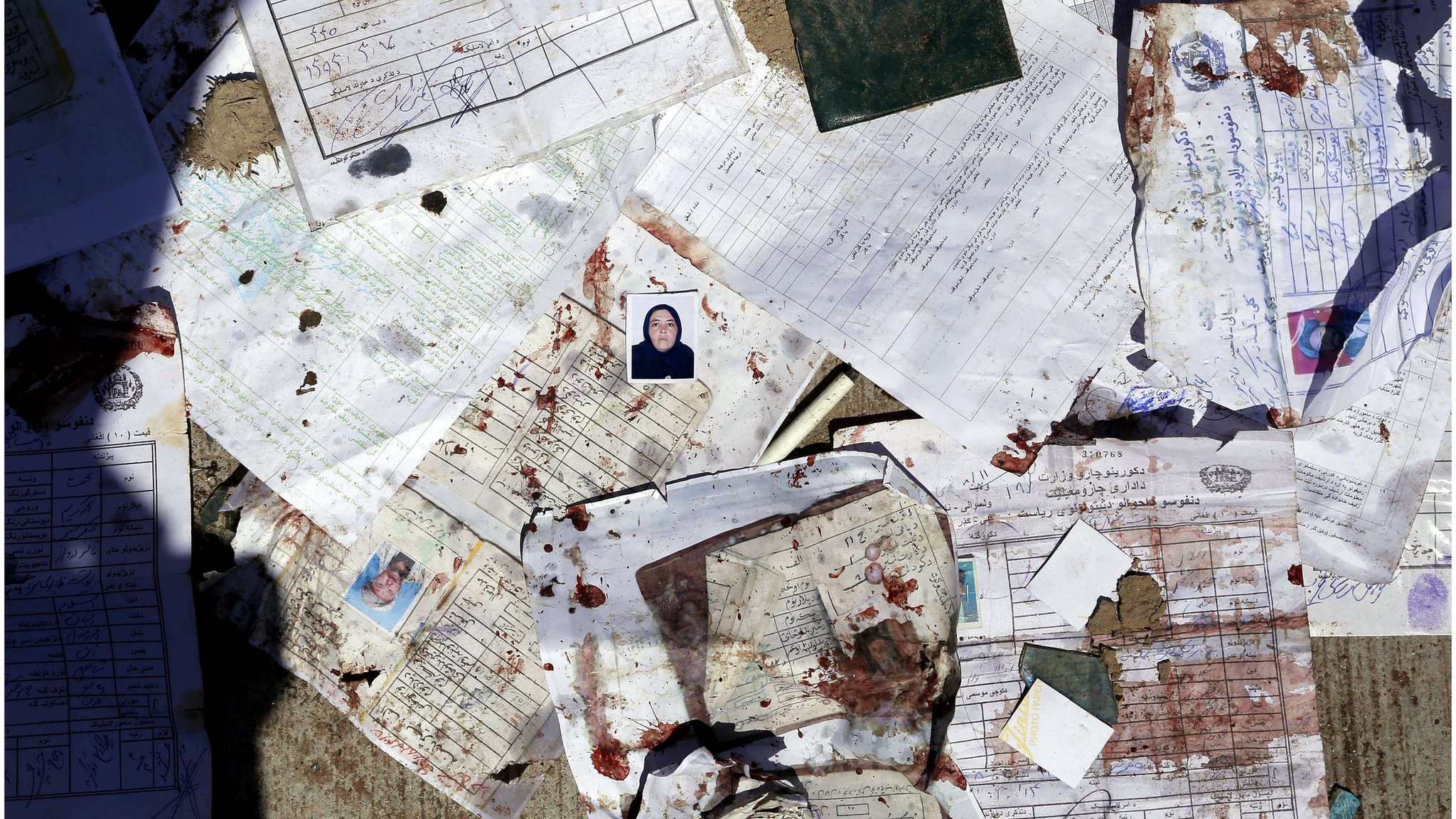 Blood stained voters' registration papers are seen on the ground at the scene of a suicide bomb attack that targeted a voter registration centre in Kabul, Afghanistan, 22 April 2018