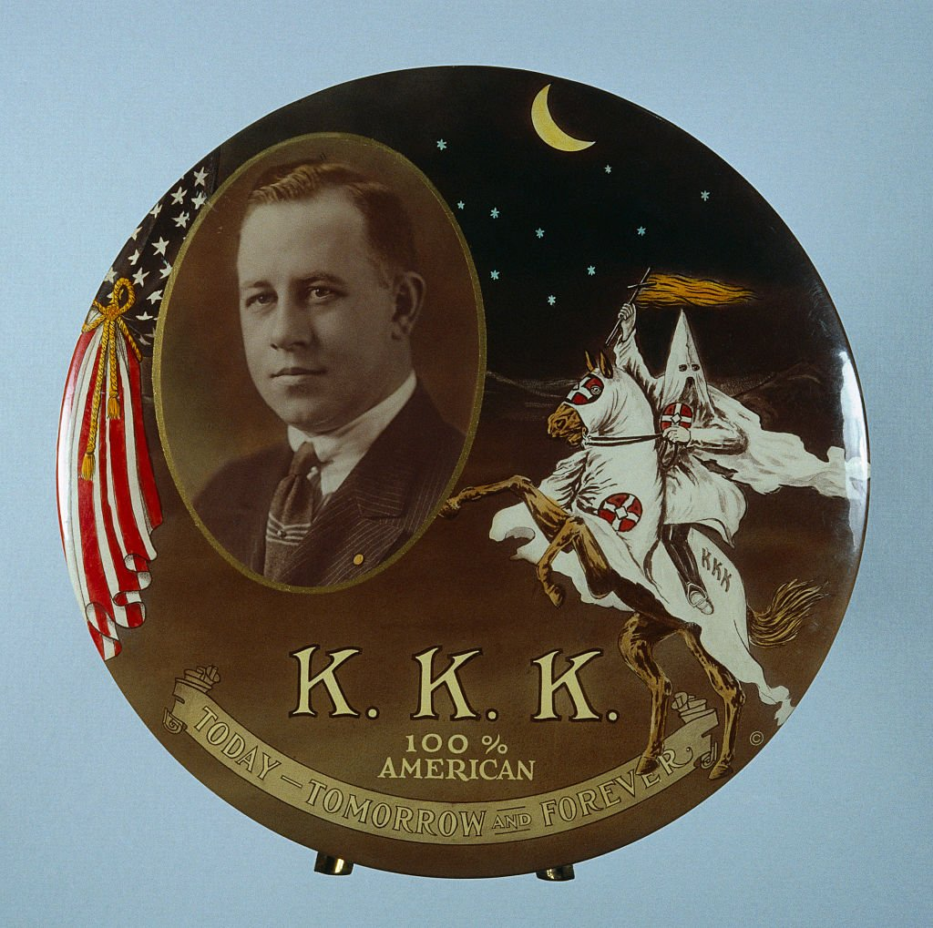 """Pendedor que muestra a Hiram W. Evans, mago imperial del Ku Klux Klan (KKK), en la década de 1920, y el lema """"KKK, 100 por ciento estadounidense, hoy, mañana y siempre""""."""