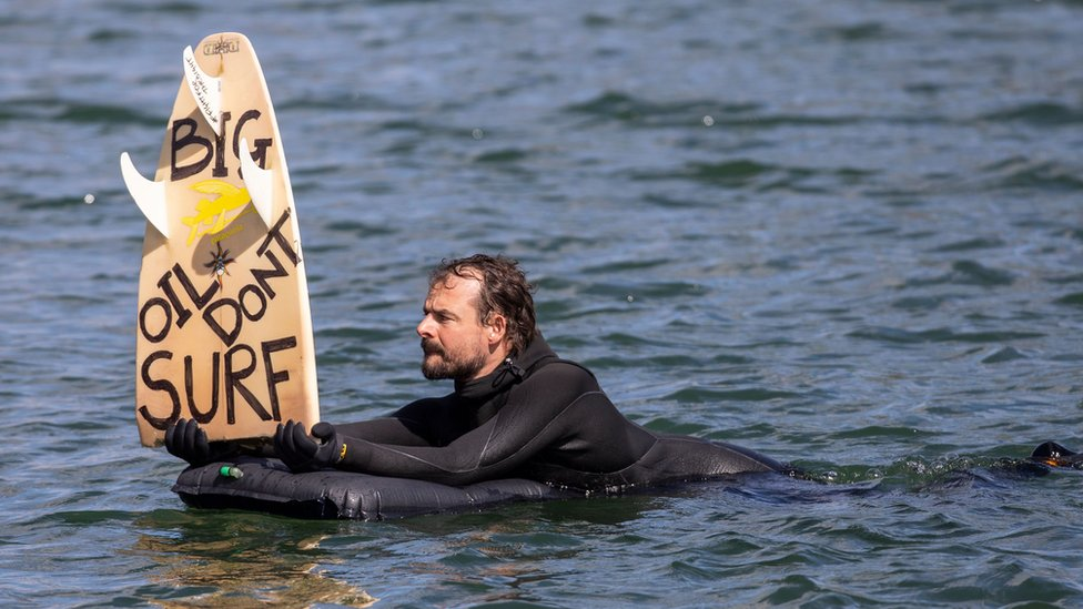 """A protester in the harbour in Oslo, Norway holds up a surfboard with the political message: """"Big Oil Don't Surf"""""""