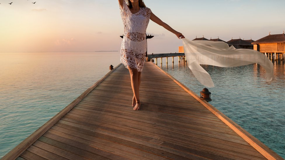 Stock image of a woman on a jetty in exotic sea resort