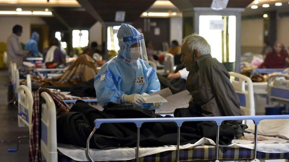 Profissional de saúde paramentado atende idoso em hospital de Nova Déli