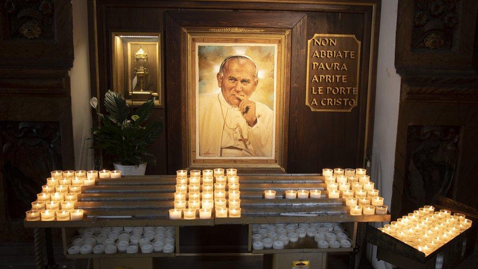Свічки біля портрета Папи Римського