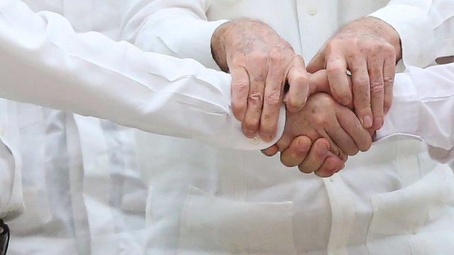 Close up of hands as Colombian president and FARC leader shake hands (with Cuban leader's hands holding both of them)