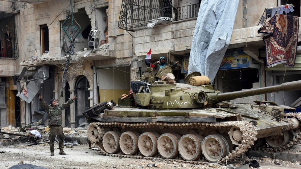 Syrian army soldiers make victory signs in the Sukkari neighbourhood, east Aleppo, Syria (23 December 2016)