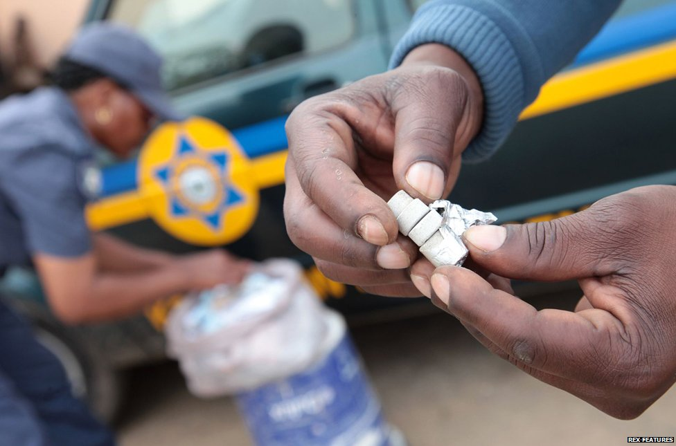 Law enforcement officers confiscating Mandrax pills