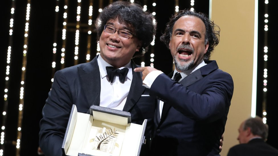"""South Korean director Bong Joon-Ho (L) poses on stage with Mexican director and President of the Jury of the Cannes Film Festival Alejandro Gonzalez Inarritu after he was awarded with the Palme d""""Or for the film """"Parasite"""" on May 25, 2019"""