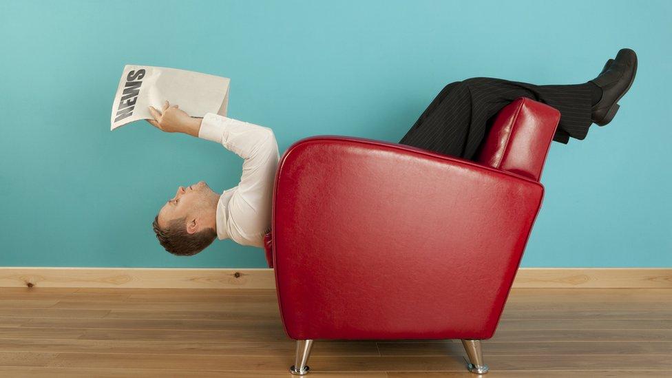 Hombre lee el diario en una posición extraña.