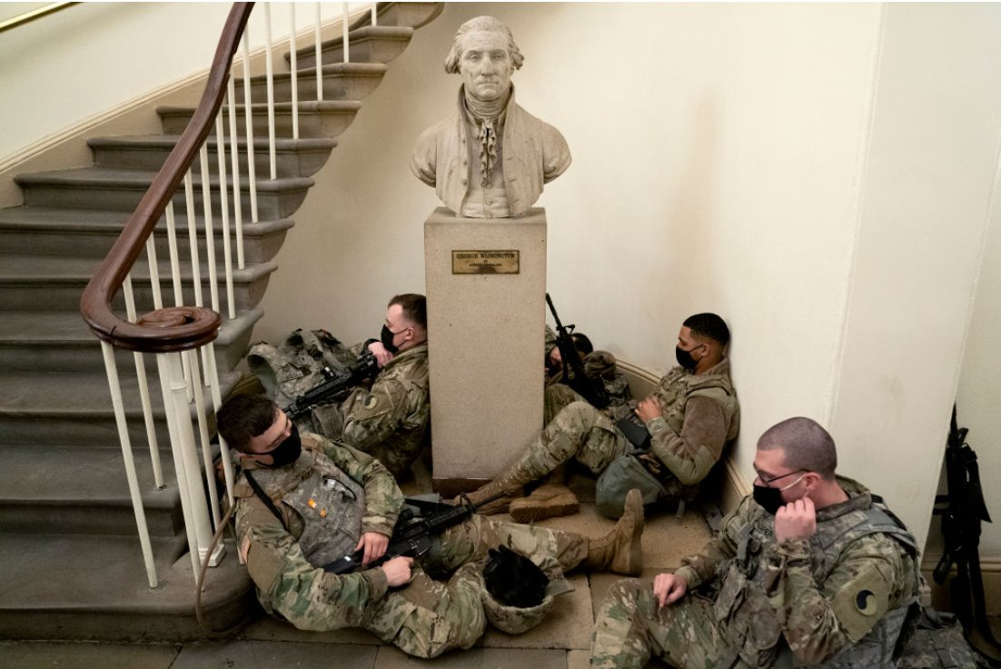 Soldiers rest against statue of George Washington