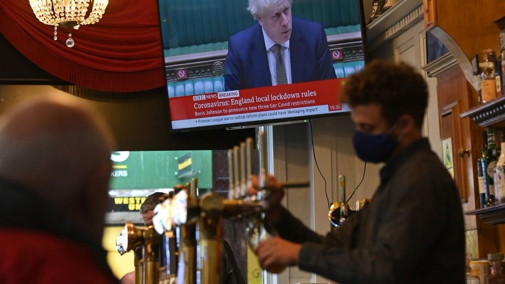 A man pours a pint whilst Boris plays in the background