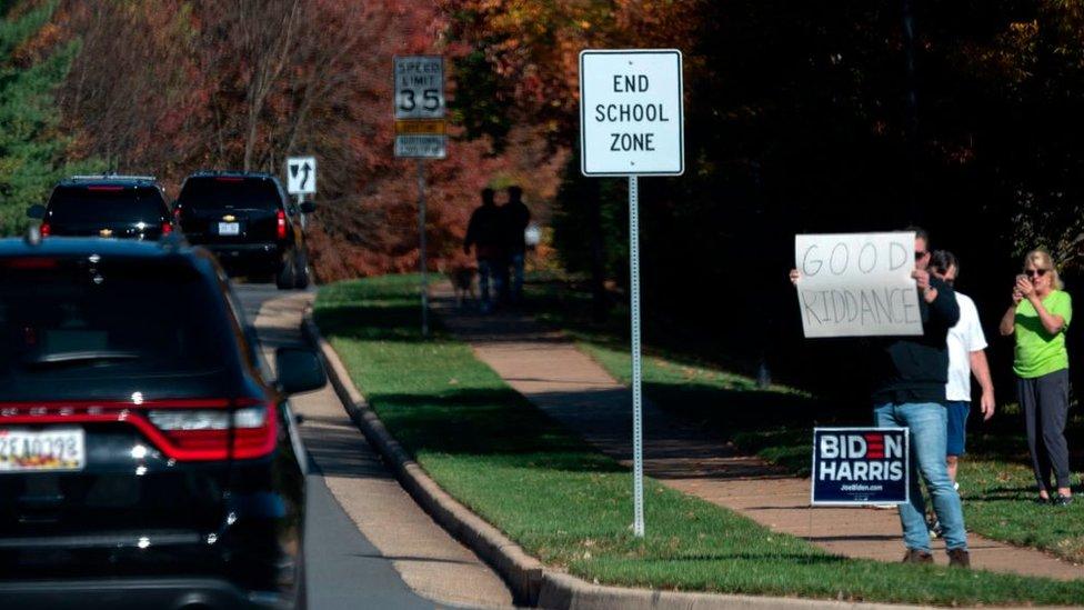 """Con un letrero de """"Hasta nunca"""" algunas personas saludaron la caravana de Trump en el Sterling (Virginia)."""